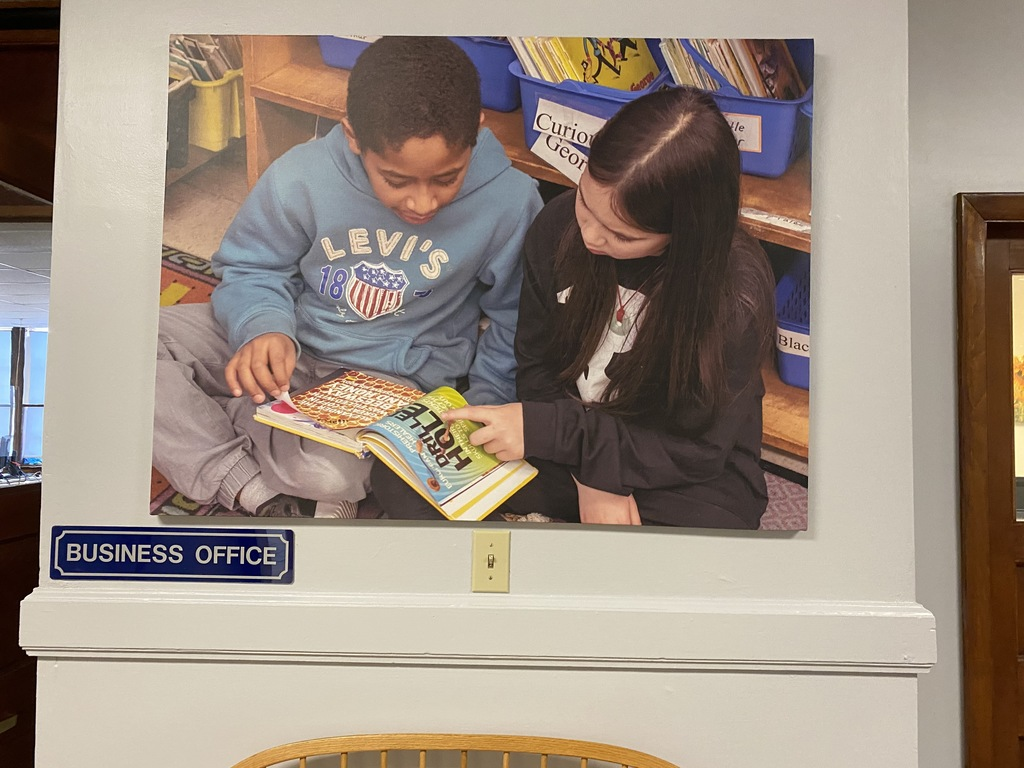 picture of 2 students with book in hallway