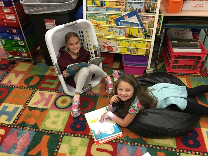 girls reading--one in laundry basket and one on beanbag