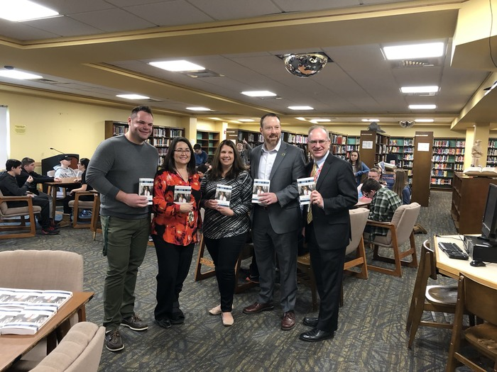 SHS Teachers, principal, and Fidelity community partner holding books donated to the Freshman class.