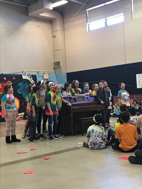 students performing near a piano