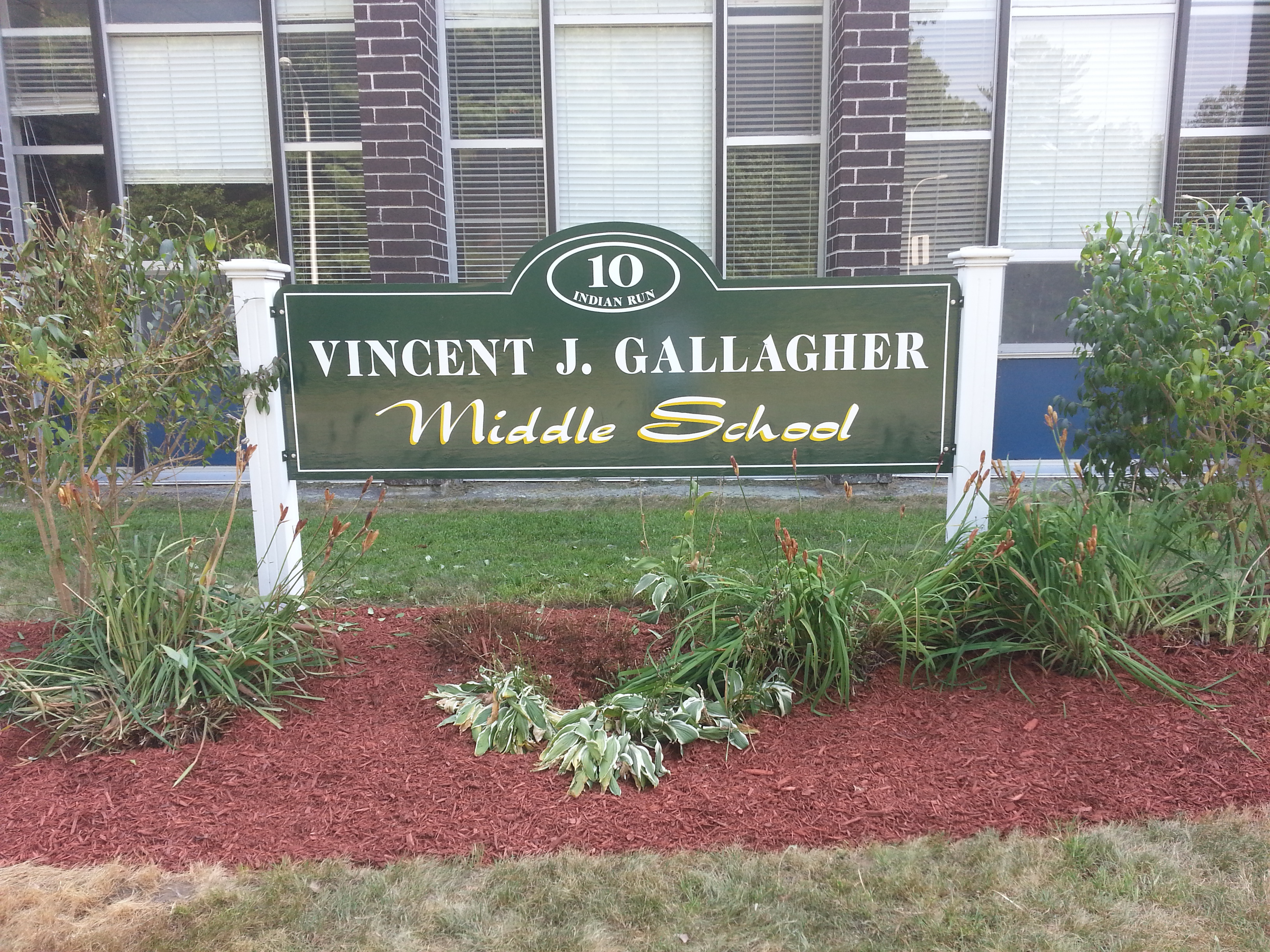 Green sign with white and yellow lettering reading Vincent J. Gallagher Middle School